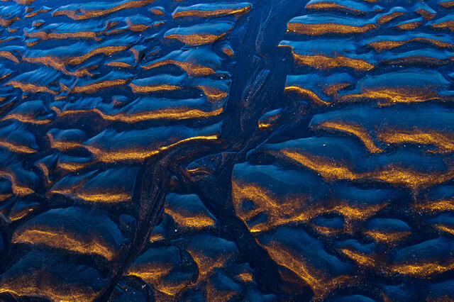 Reflections in the sand on the black sand beach below Vesterhorn Mountain in southeast Iceland.