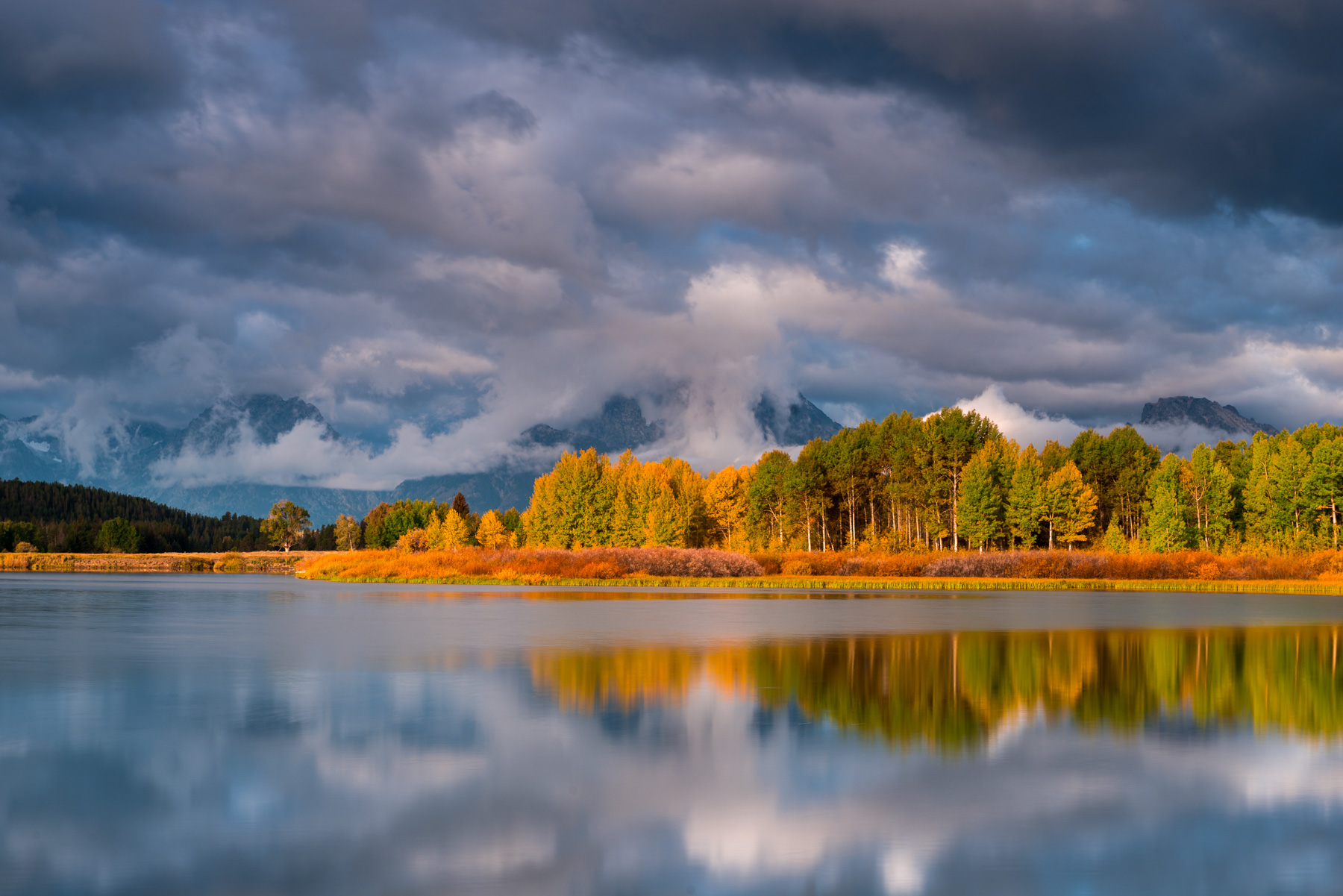 A stormy sunrise reflected in the still waters of Ox Bow Bend, Grand Teton National Park, Montana. Available Print Sizes: 12x18...