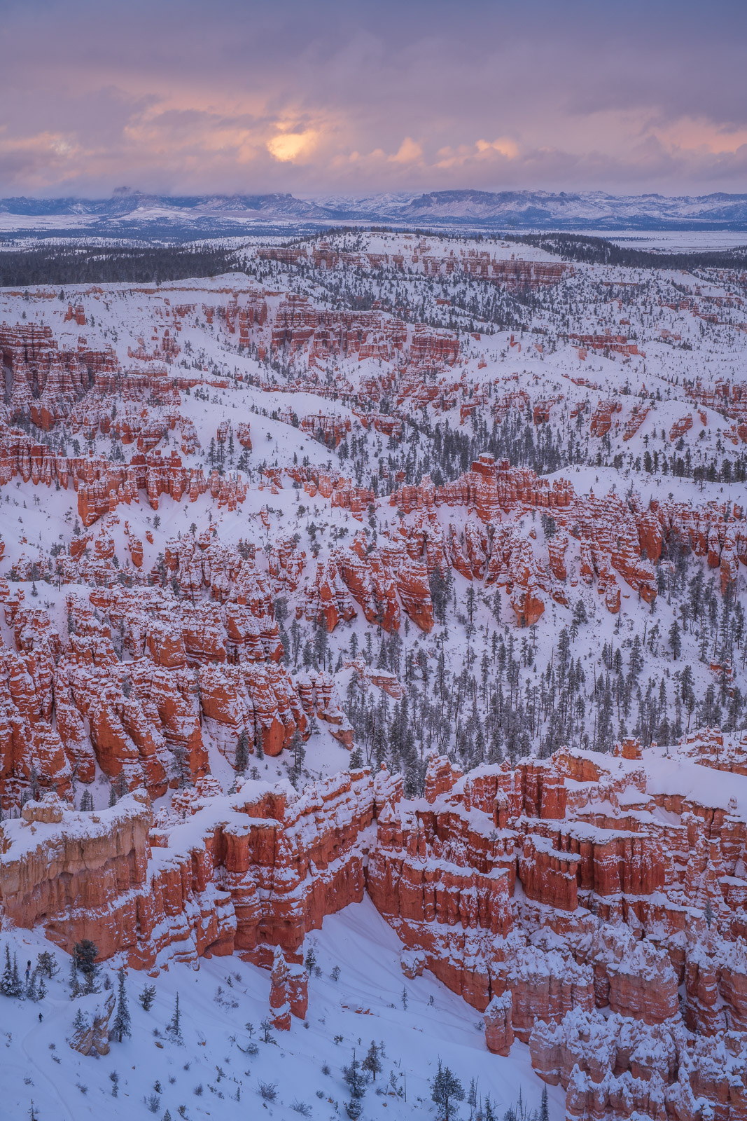 The storm that dumped a foot of snow on Bryce Canyon begins to break up at sunset.