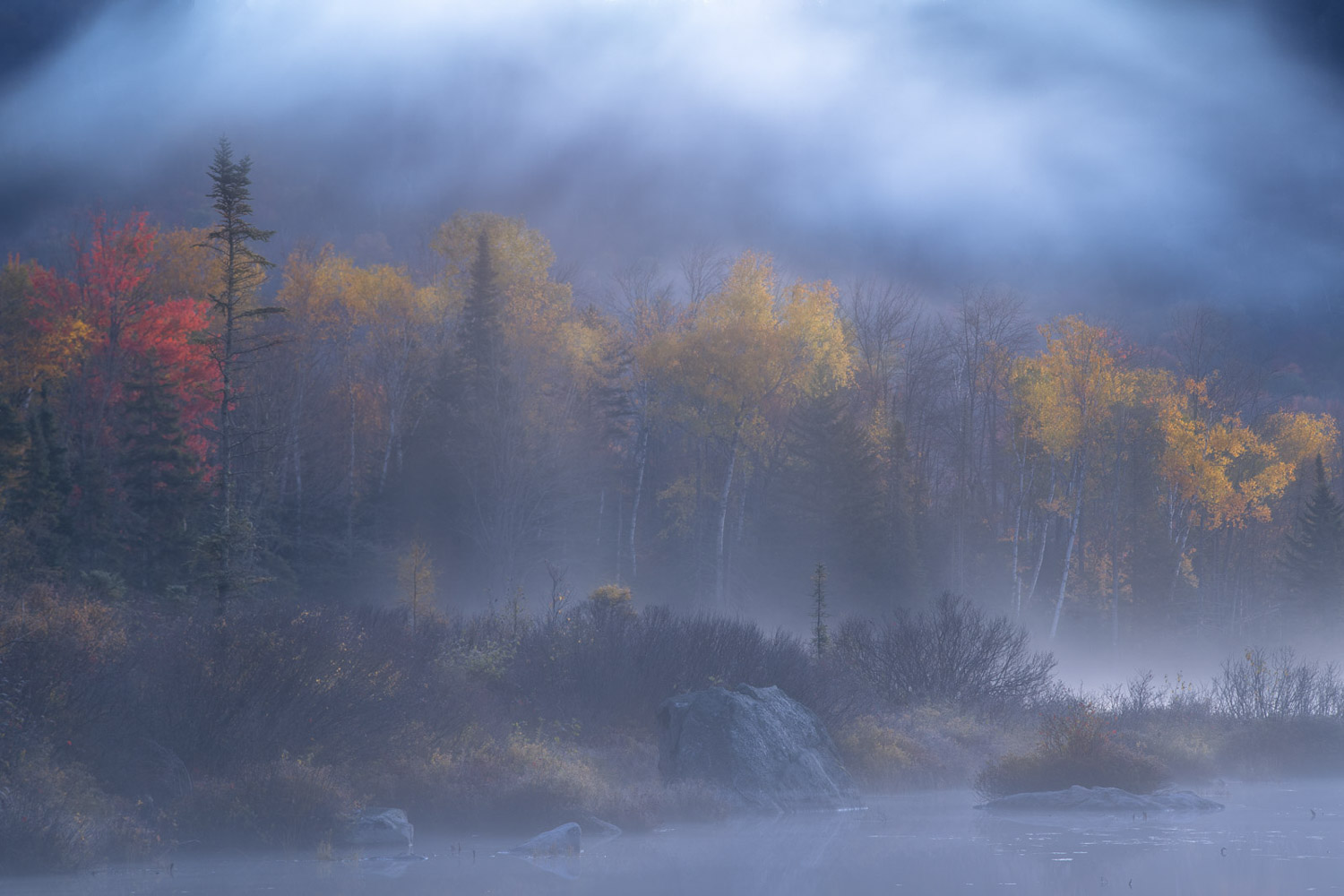 Morning fog and autumn colors at twilight on a pond in Vermont.