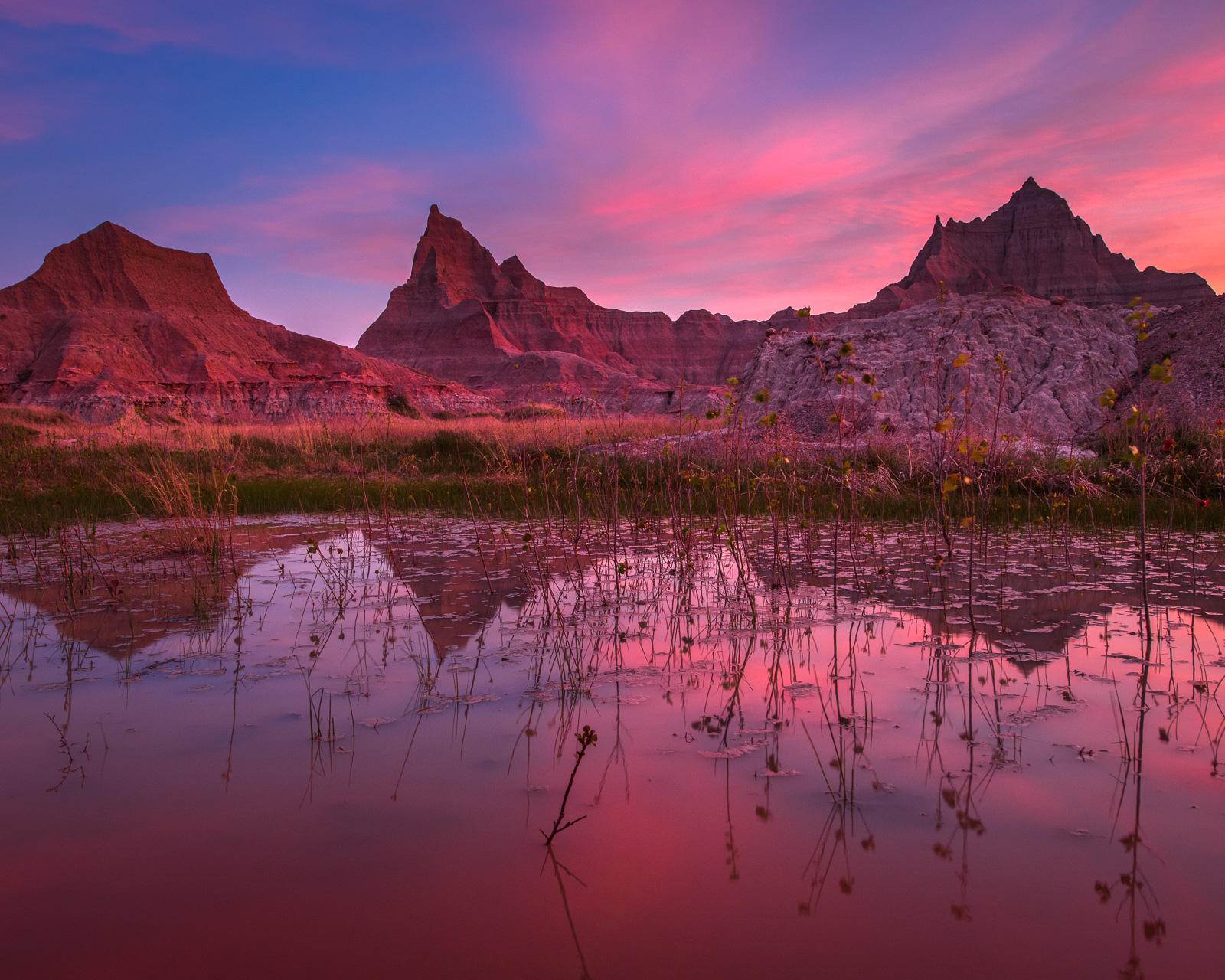 Summer rains bring pools of water to the prairie and allowed me to capture this stunning sunrise with the pinacles and towers...
