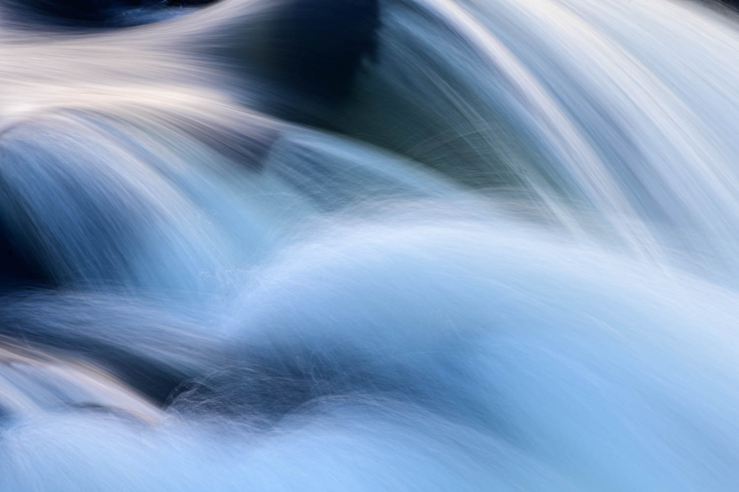 This photo depicts rushing water falling over rocks in Great Falls National Park, Virginia.