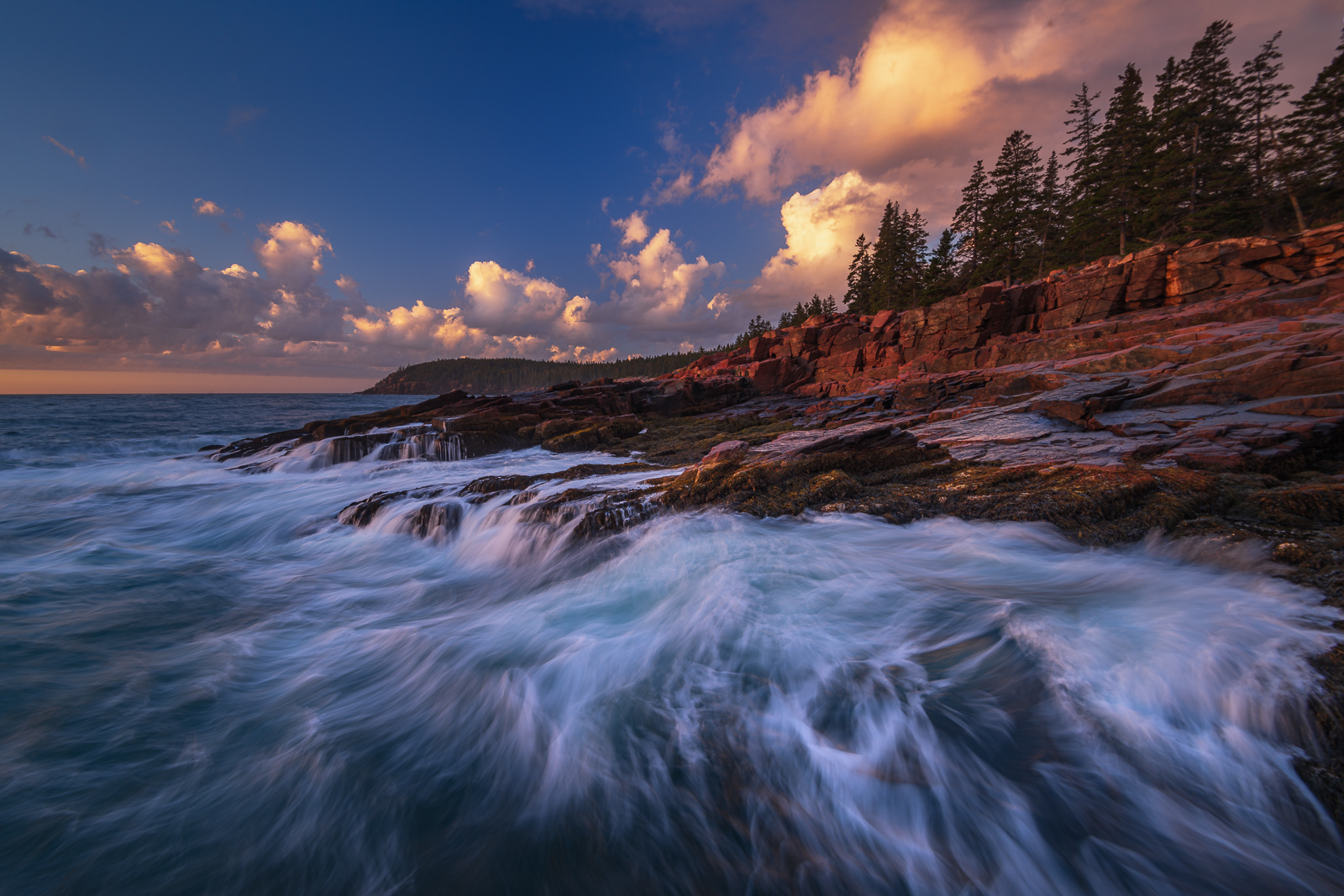 Breaking waves at sunrise along the rugged granite coast of Acadia National Park.