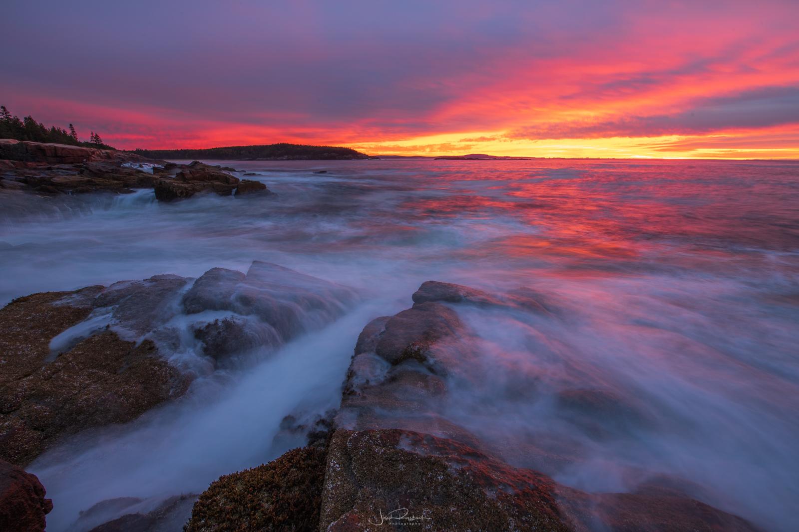 Breaking waves along Acadia's rugged coastline at sunrise.
