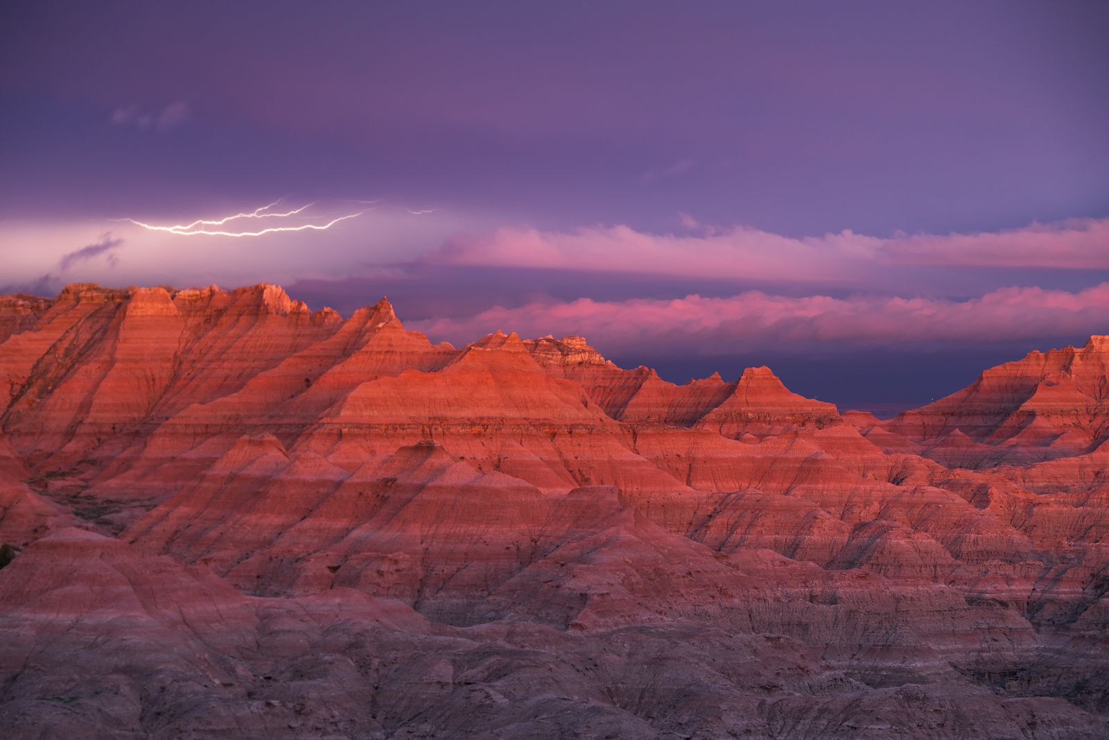 Lightning over the Badlands at sunset during a passing summer thunderstorm.