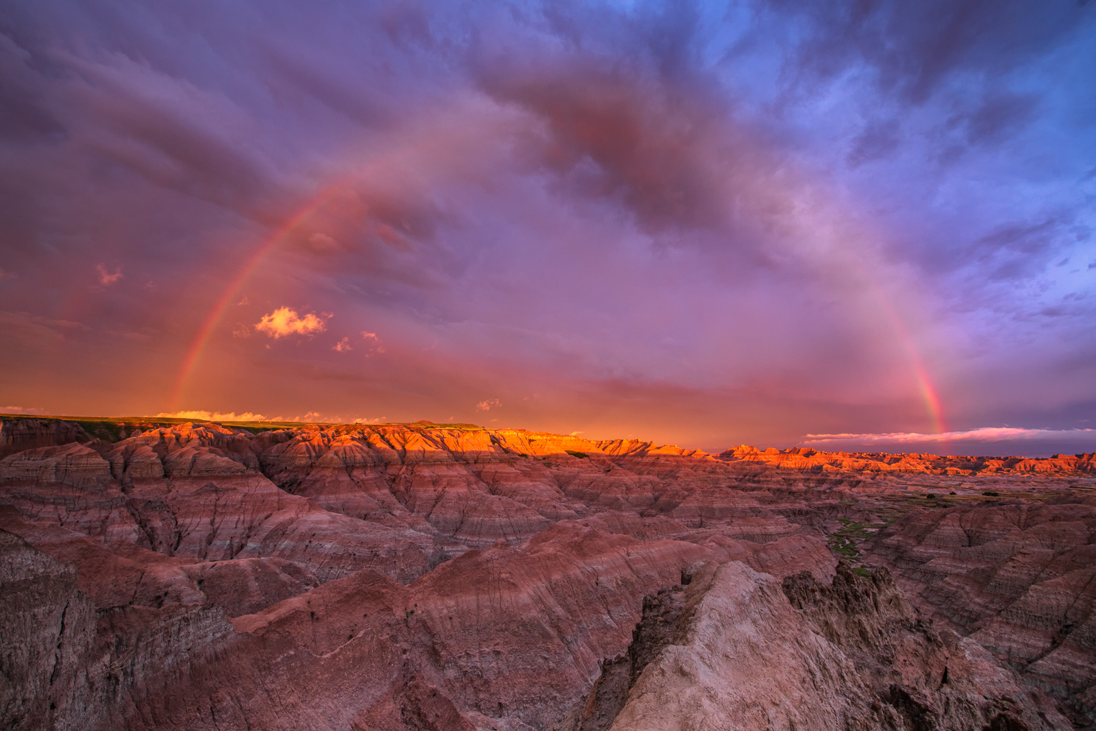 A full rainbow arcing over the badlands captured dusing a violent summer thunderstorm on the prairie.