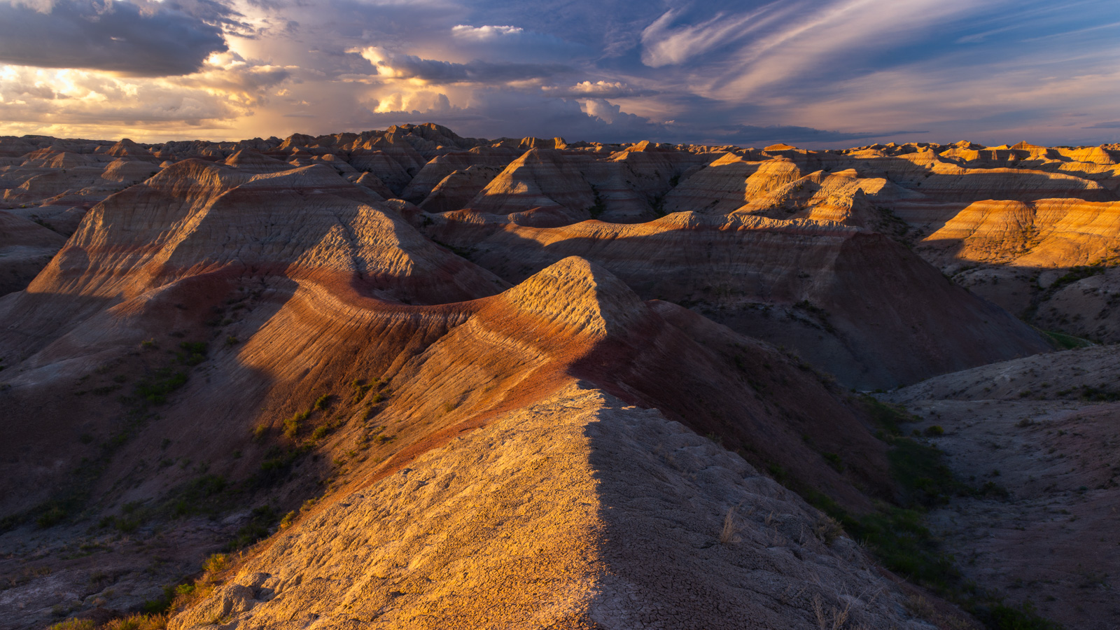 Badlands streathing for mailes as a huge thunderstorm develops at sunset.
