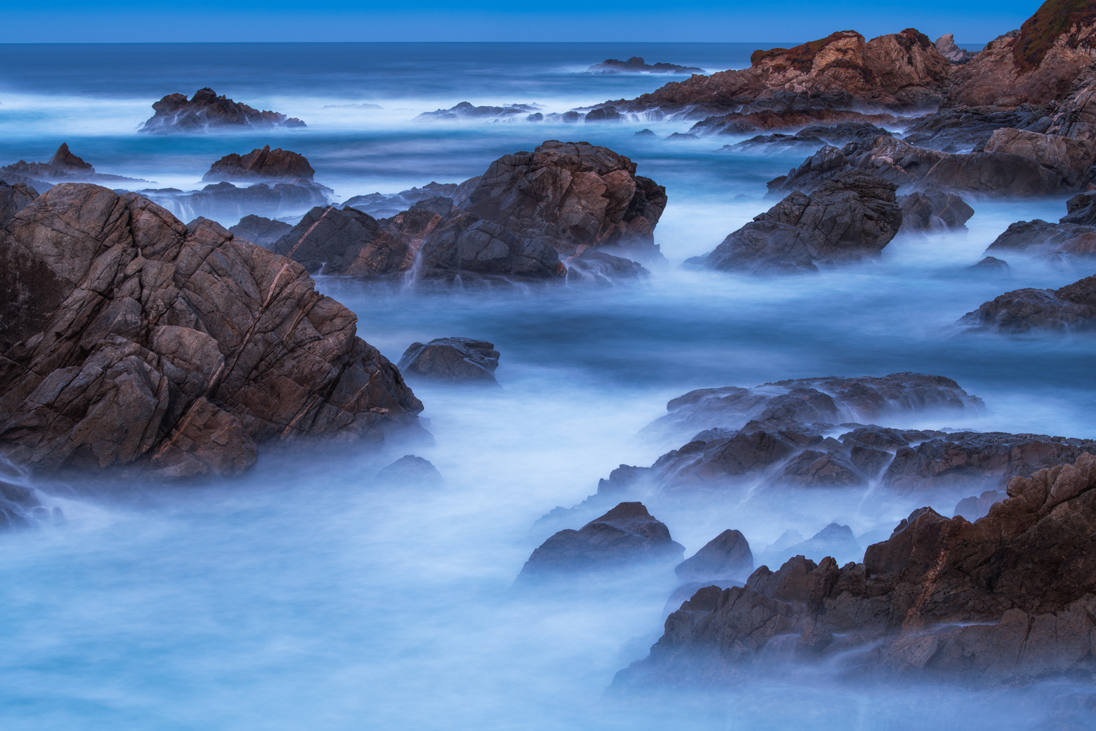 A long exposure at twilight captures a haunting feel along Big Sur's rugged coastline.