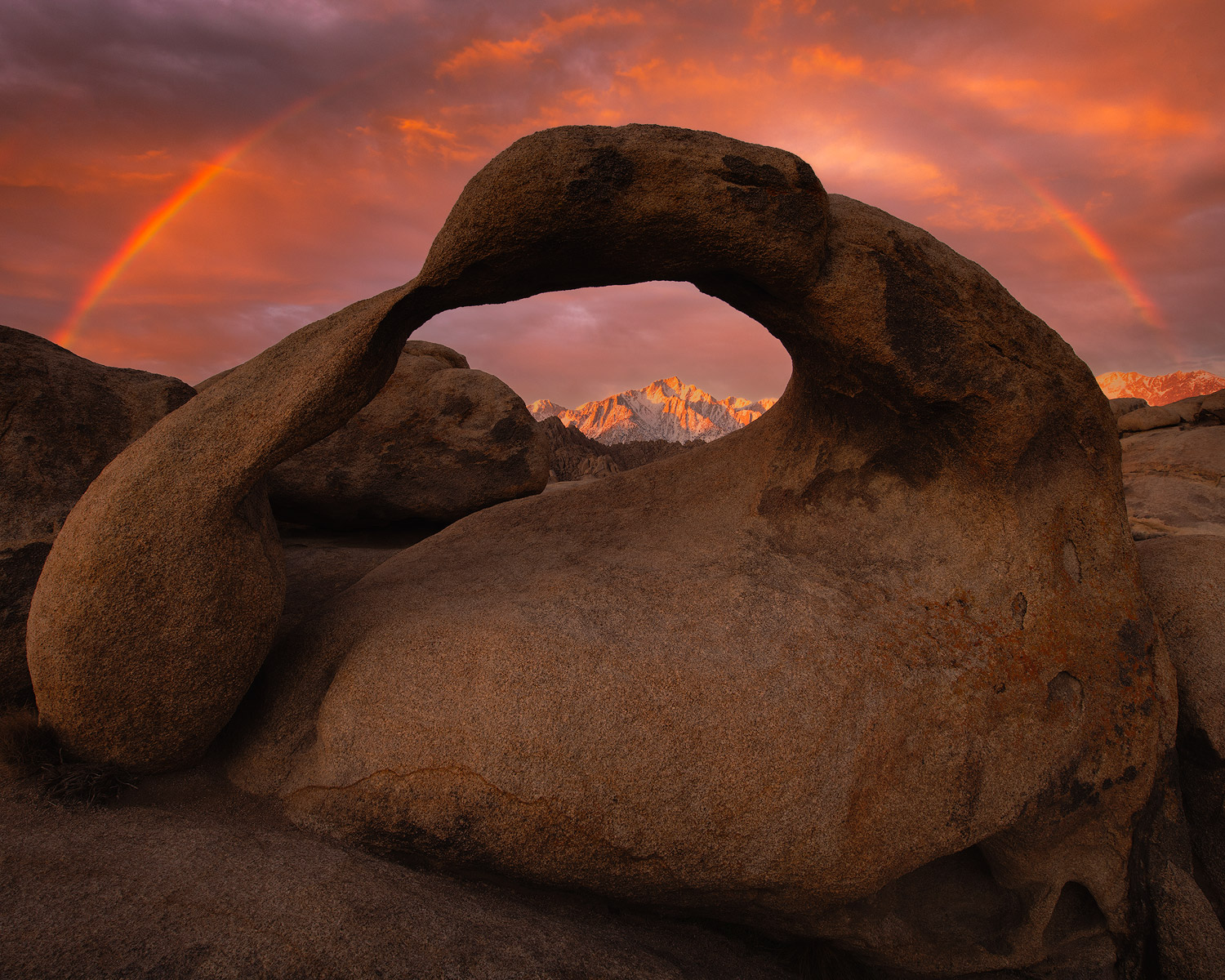 Mobius Arch frames Lone Pine Peak with a dramatic sunrise illuminating the peaks and rainbow above the arch. I spent many years...