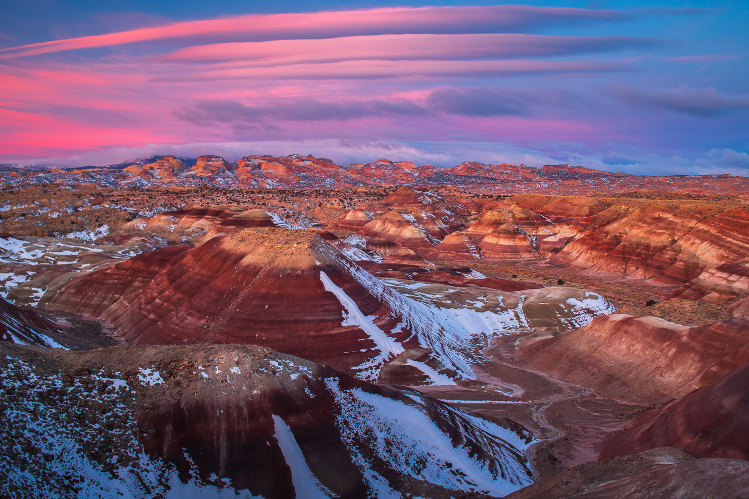 Bentonite Badlands before the Capitol Domes of Capitol Reef National Park at sunrise.