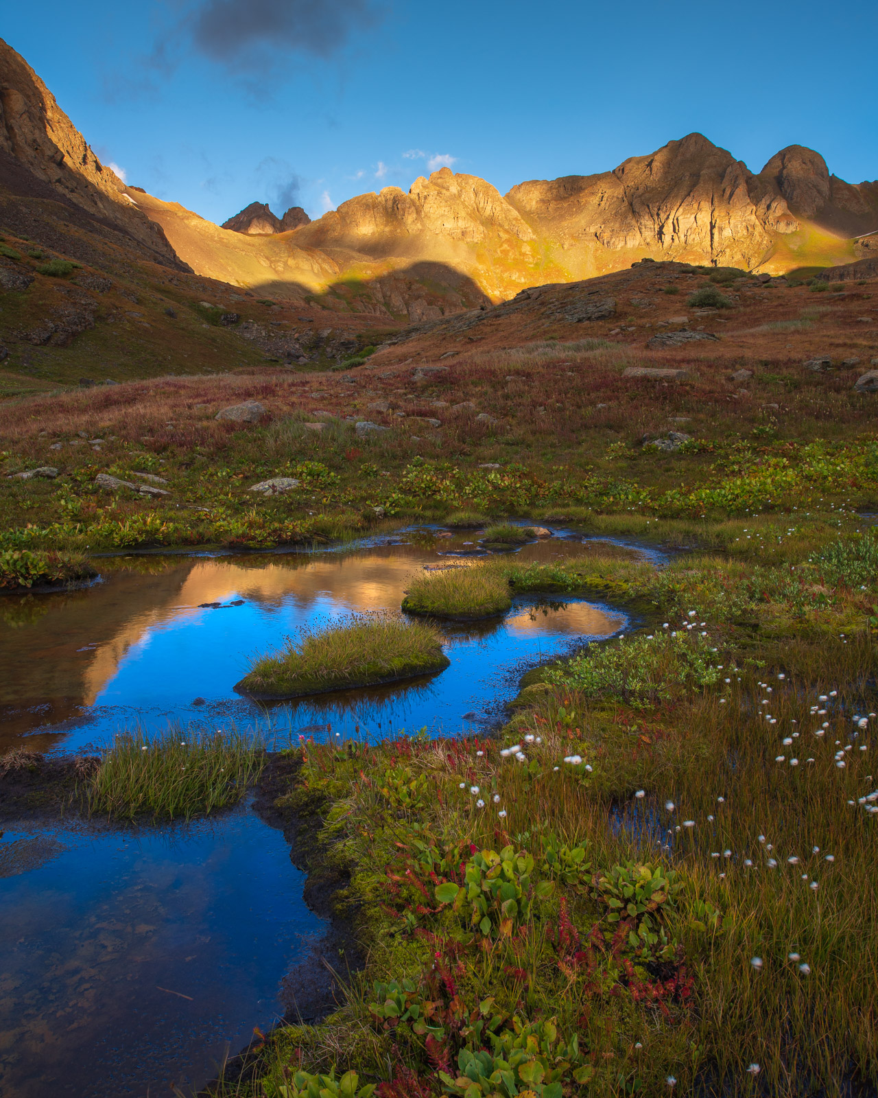 Alpine tundra and reflections of massive rocky peaks in Clear Lake Basin, Colorado.