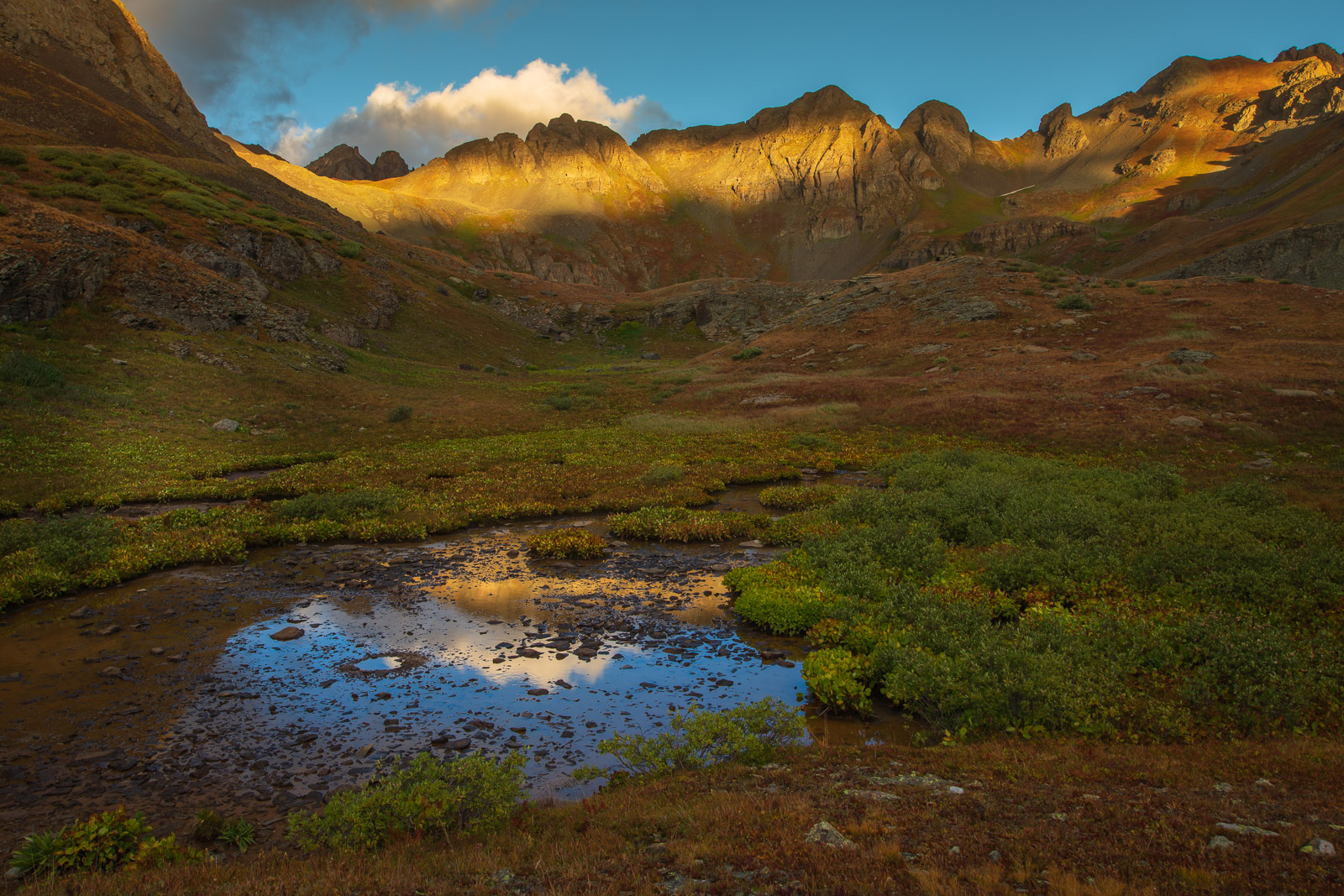Early autumn tundra and reflections of massive granite peaks in Clear Lake Basin, Colorado.