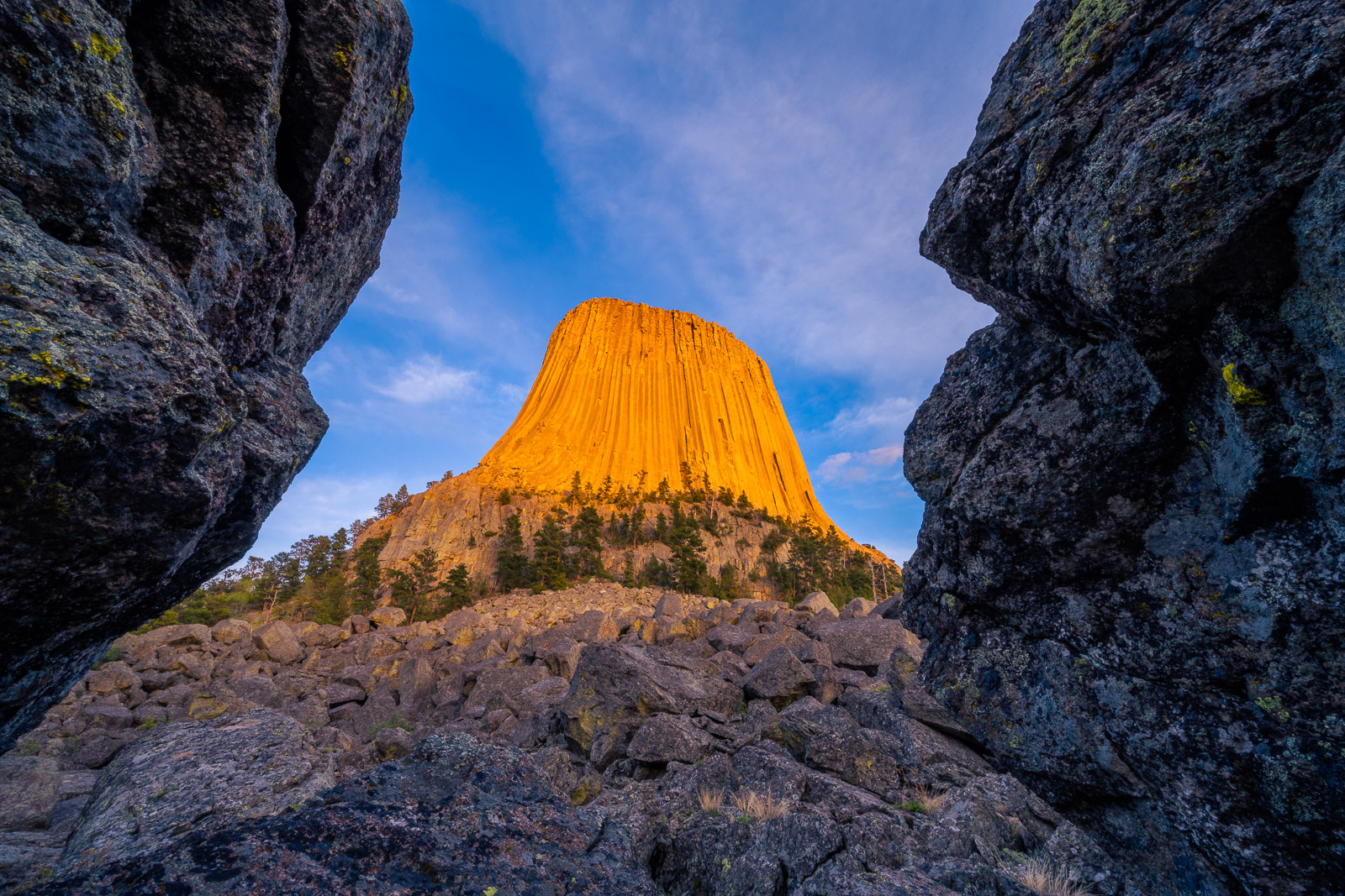 Devils Tower at sunset framed by two large boulders.