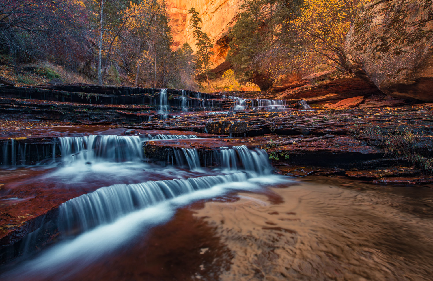 Waterfalls over red sandstone ledges before the Subway Slot Canyon.
