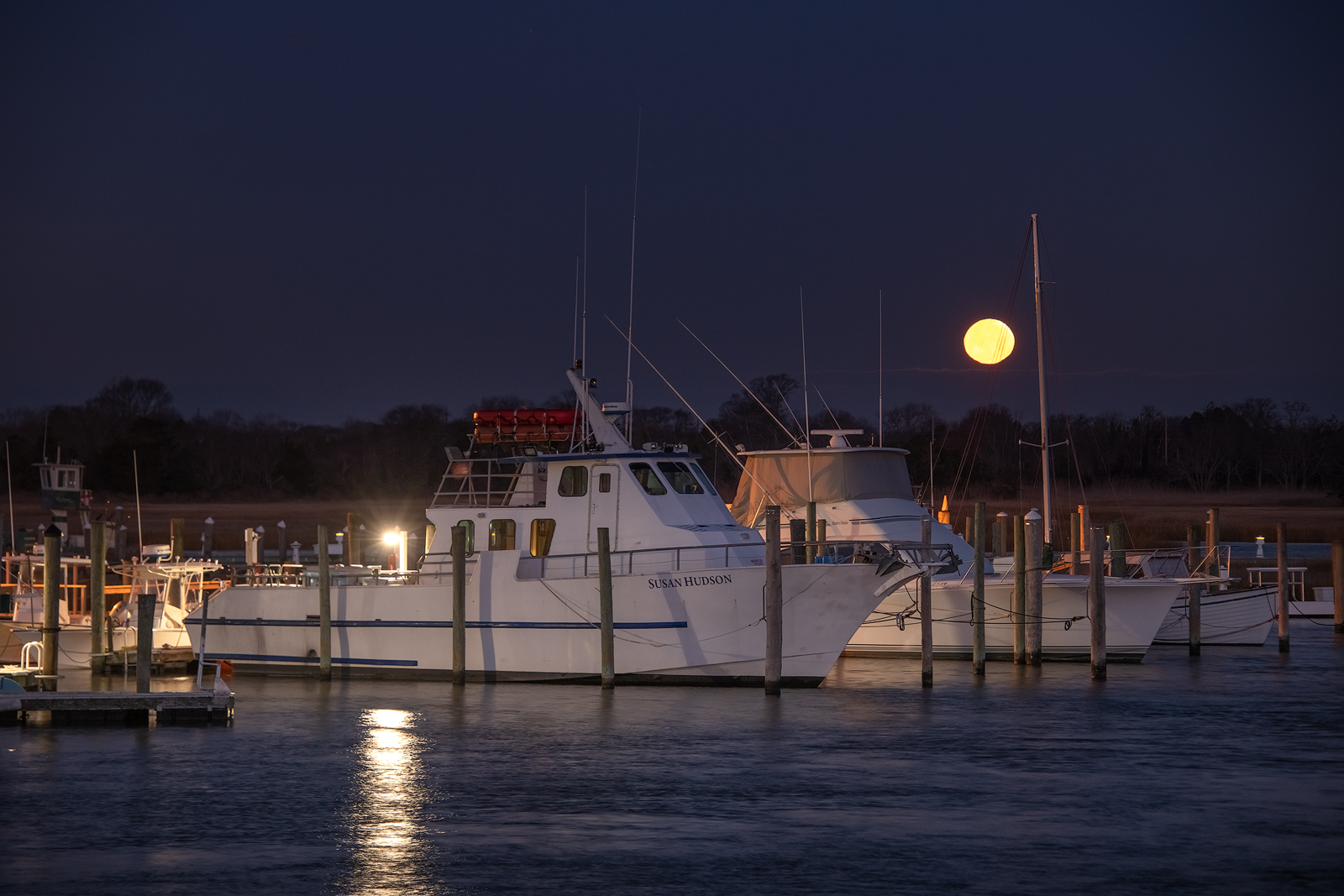 Fishing boats at dock in the harbor with the Harvest Moon setting in the east.