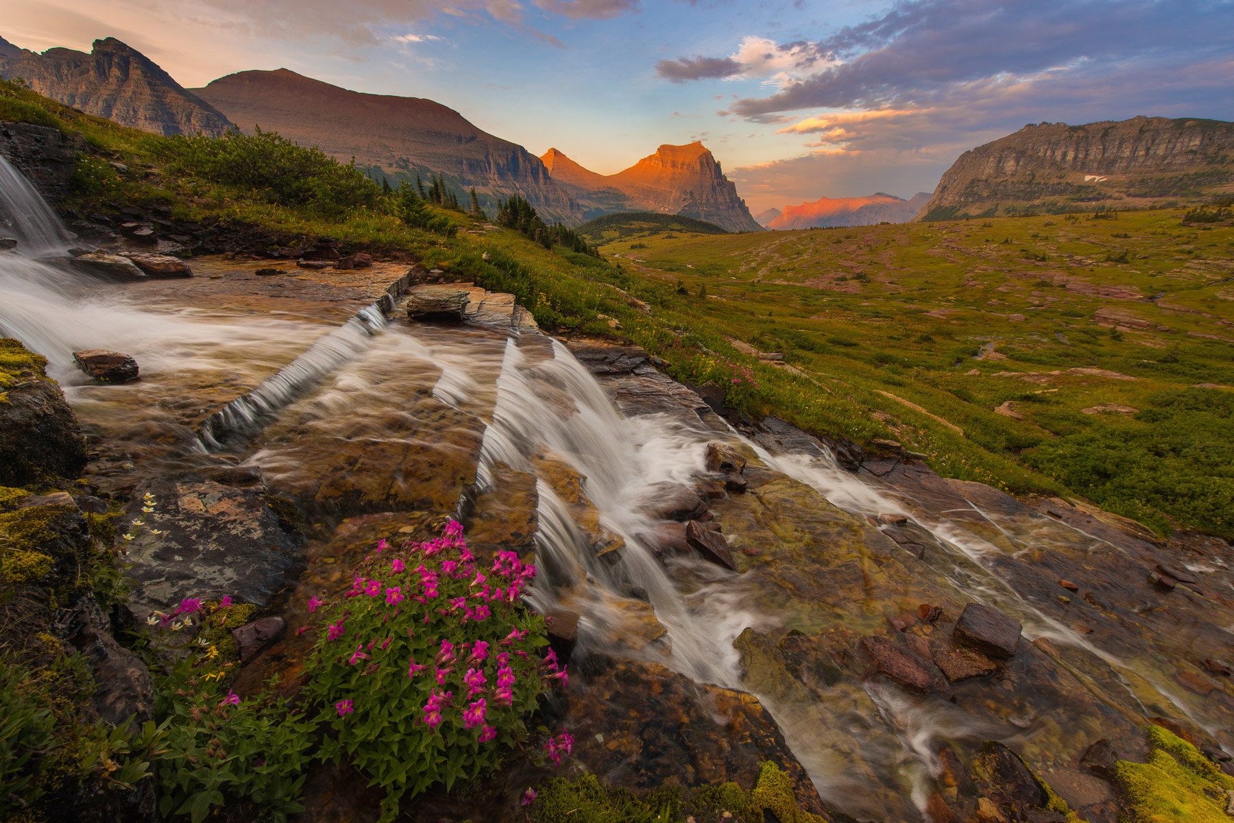 A stunning display of light captured from a remote waterfall near Logan Pass in Glacier National Park, Montana at sunset.