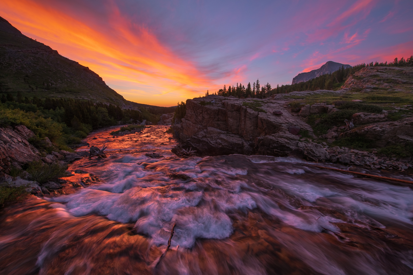 A fiery summer sunrise over the Swiftcurrent River, Glacier National Park, Montana