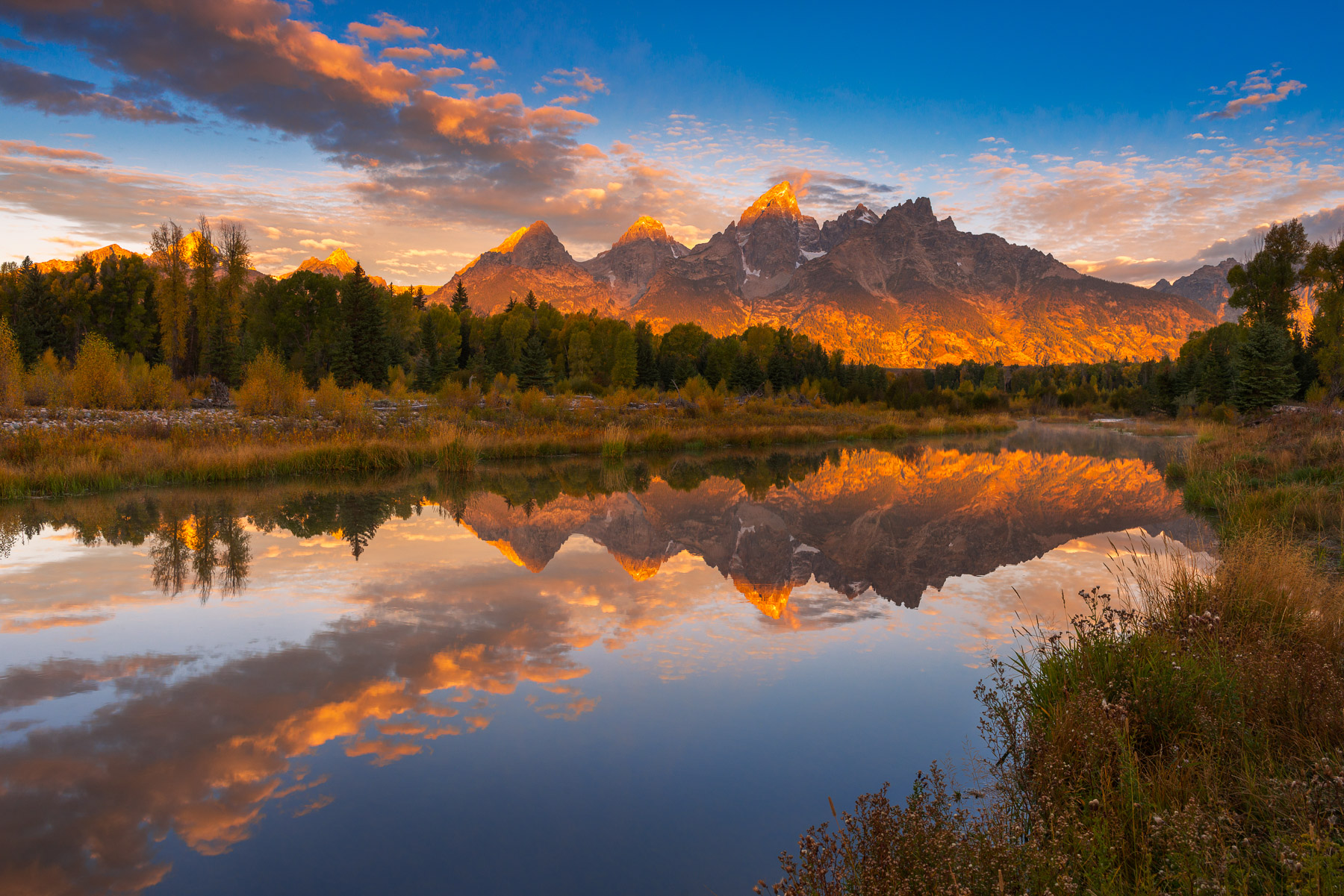 The Teton Range at sunset reflected in the still waters of Schwabacher Landing on the Snake River.
