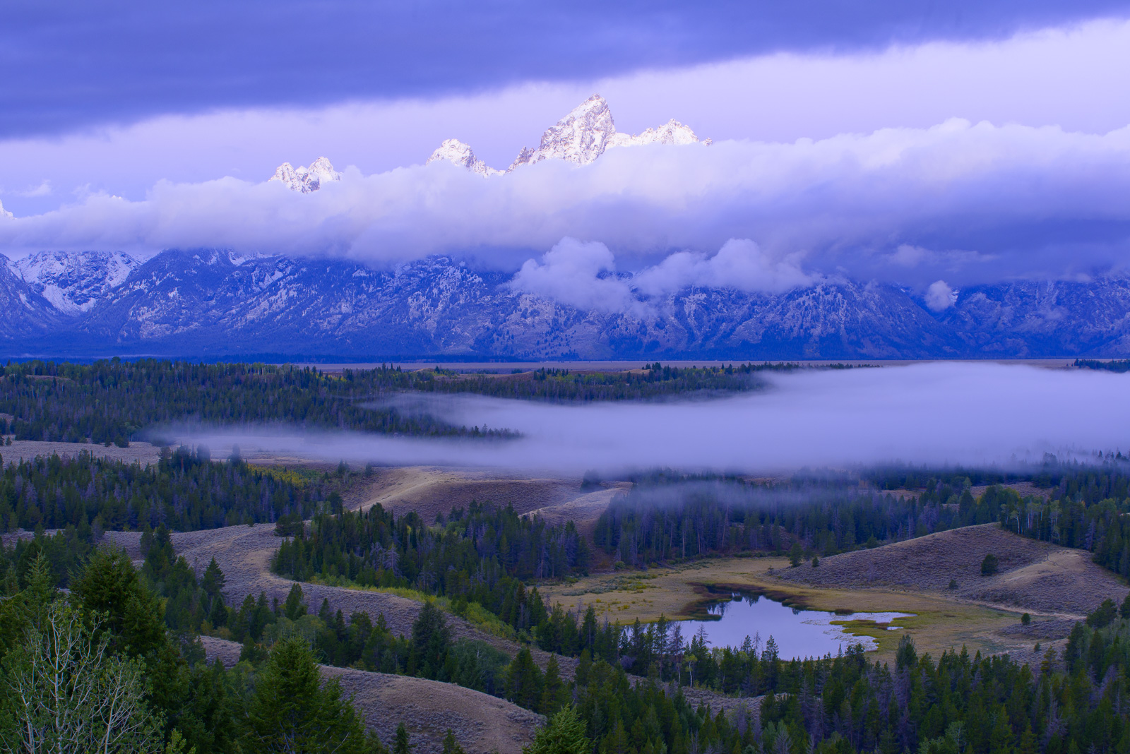 The towering peaks of the Grand Tetons make a brief appearence at dawn on a frigid autumn morning.Add beauty to your space with...