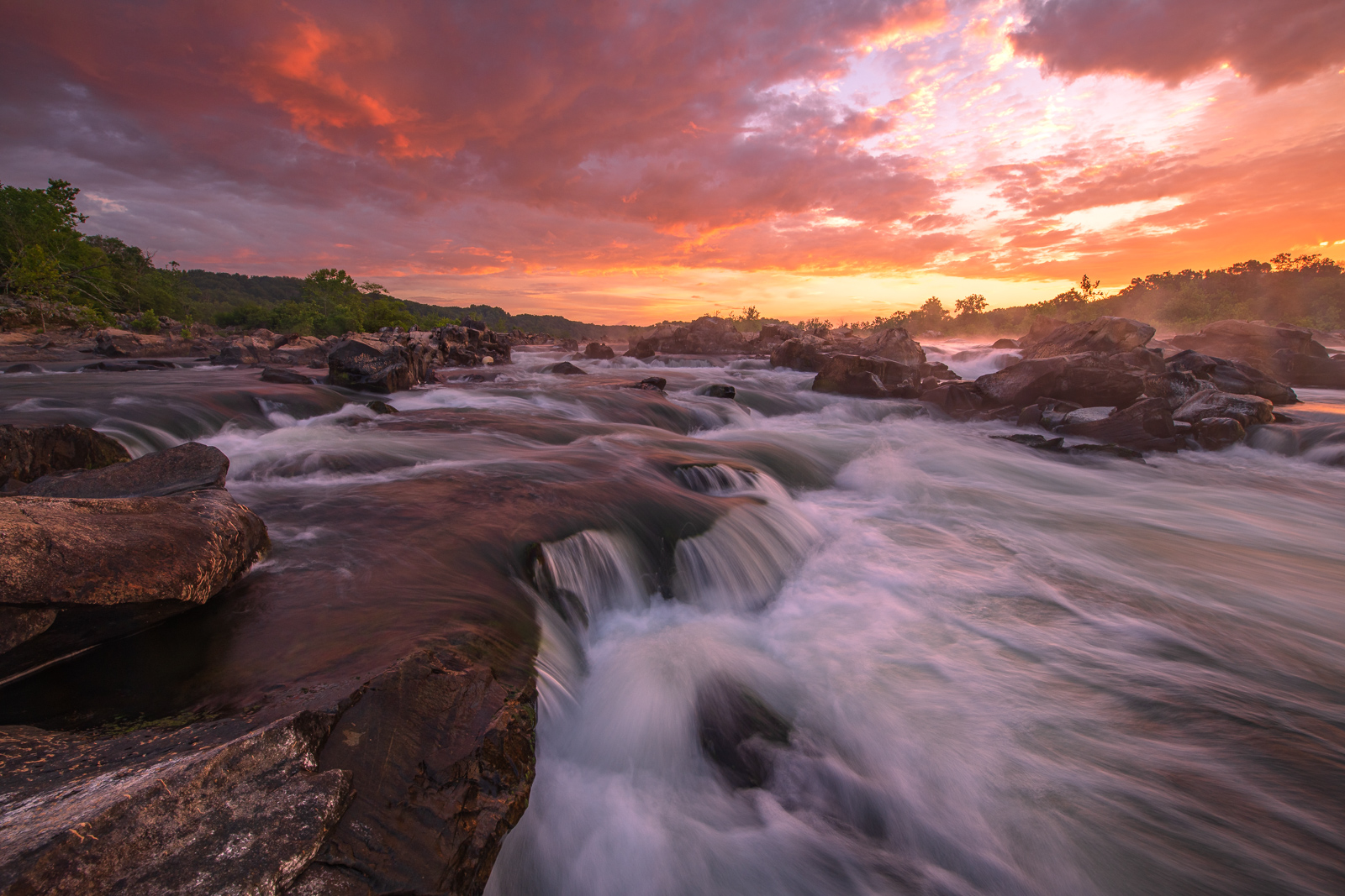A spectacular summer sunrise on the Potomac River in Great Falls National Park, Virginia.
