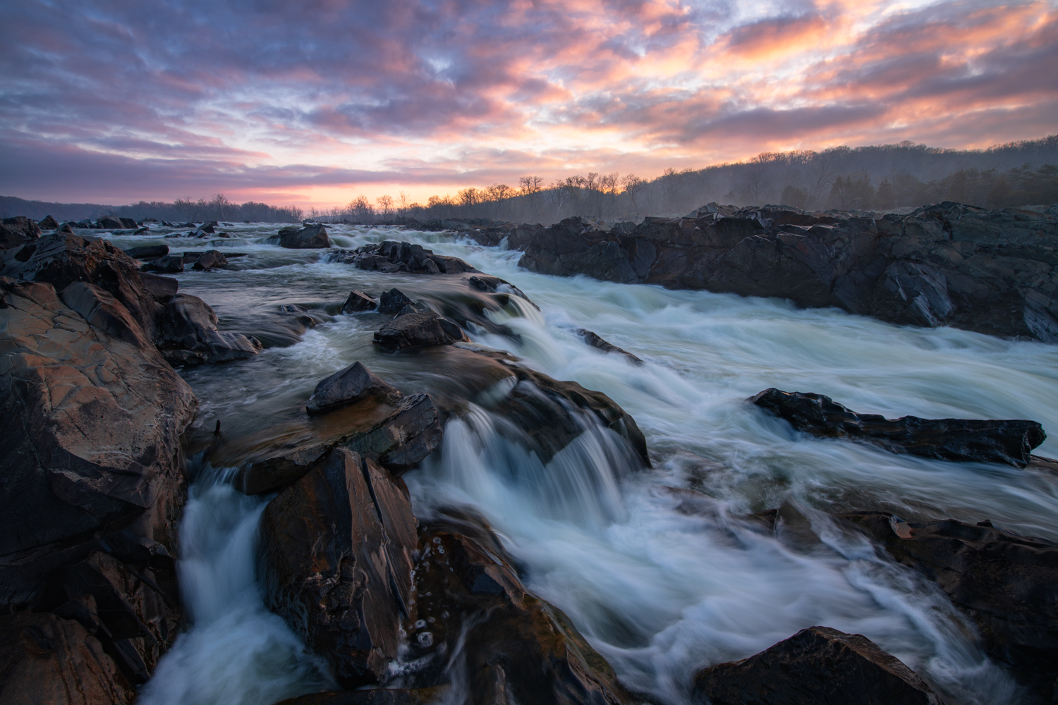 Intense sunrise color abover the waterfalls of Mather Gorge in Great Falls BNational Park, Virginia
