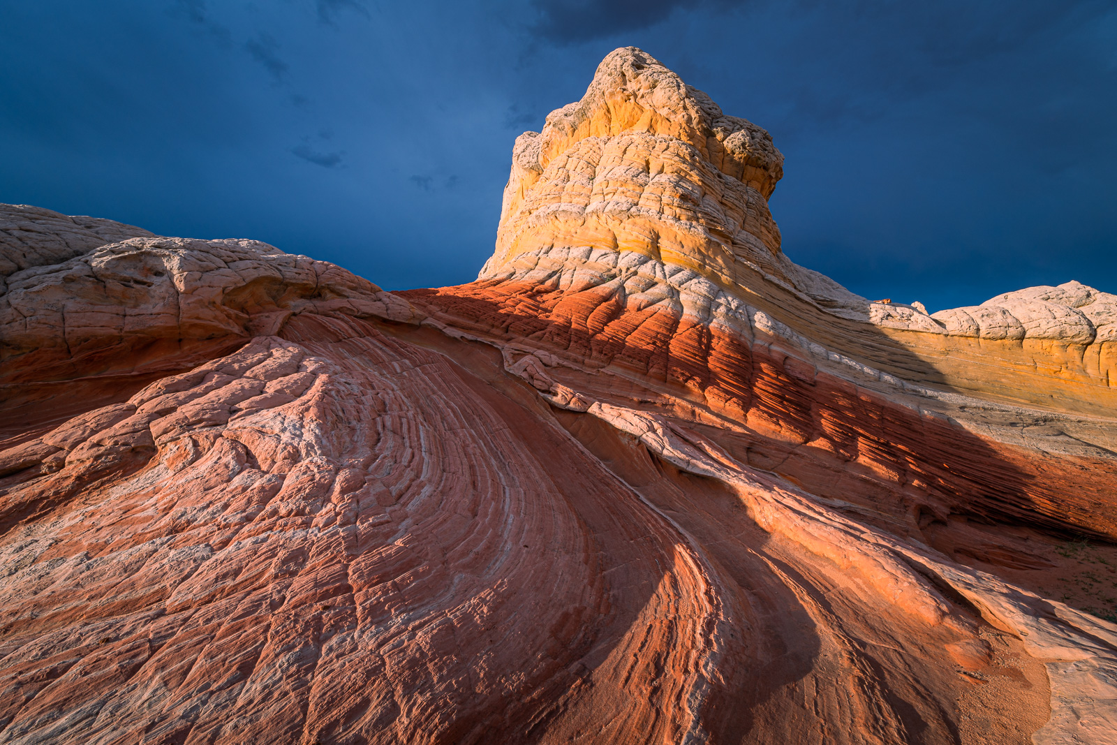 Bizarre sandstone formations at sunset under menacing storm skies from a remote location known as White Pocket.