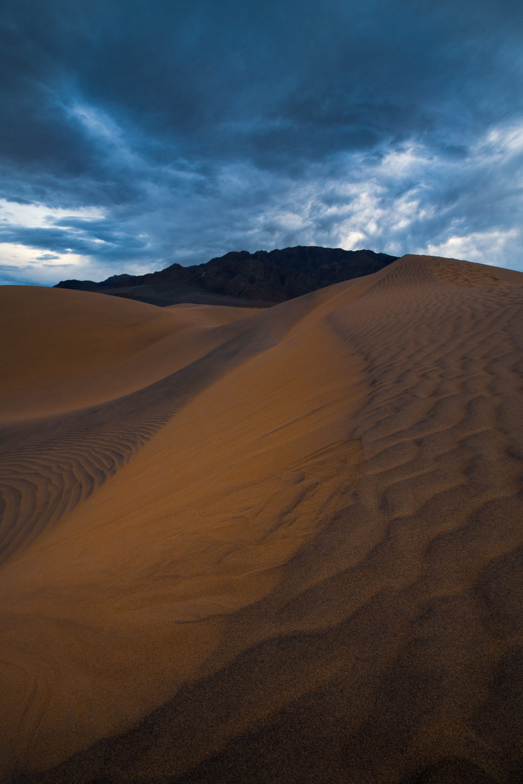Approaching storm clouds hover over the Mesquite Dunes in Death Valley.