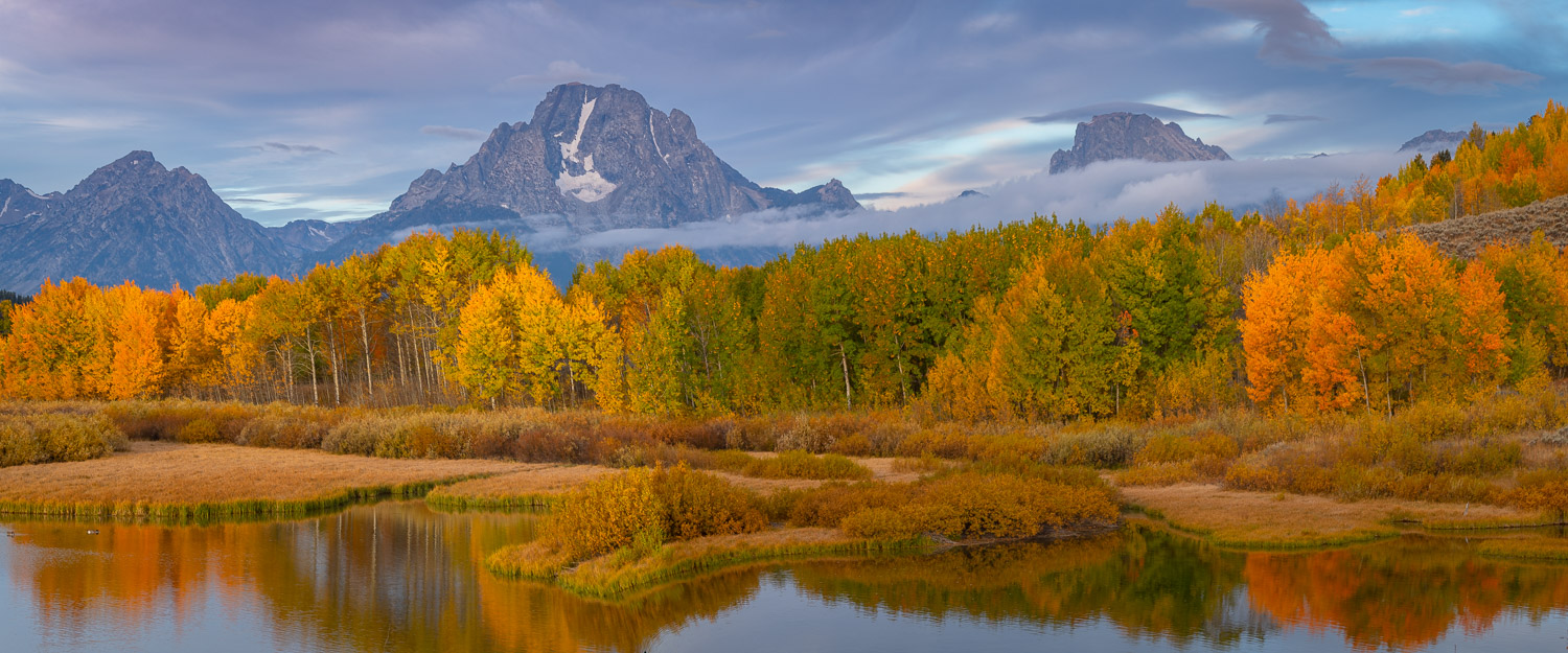 Mount Moran and the Teton Range rise above the calm waters of Ox Bow Bend. Captured at the pek of autumn cooron a cool, crisp...