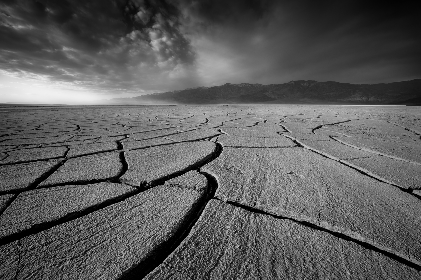 Deep Mud Cracks and the Panimint Mountain Range during a winter sand storm, Death Valley National Park, California.