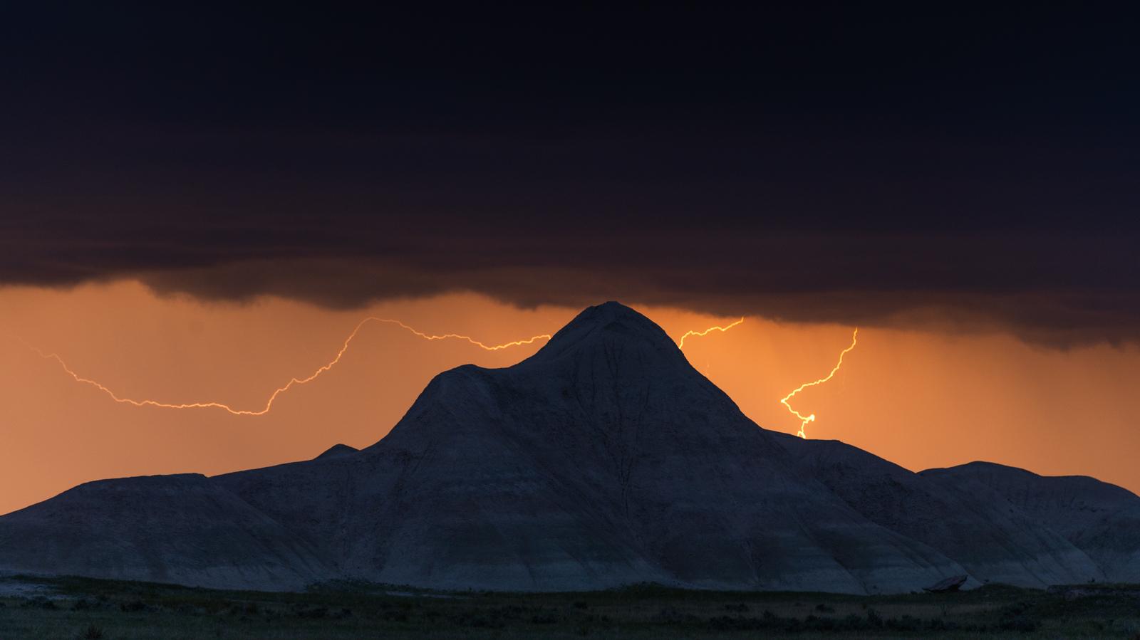 Lightning strikes against a solidary badlands butte in the Oglala National Grasslands of western Nebraska.
