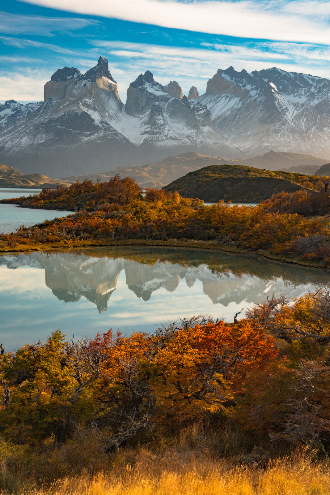 The peaks of Torre Del Paine reflected in the still waters of Lago Pehoe with stunning autumn colors