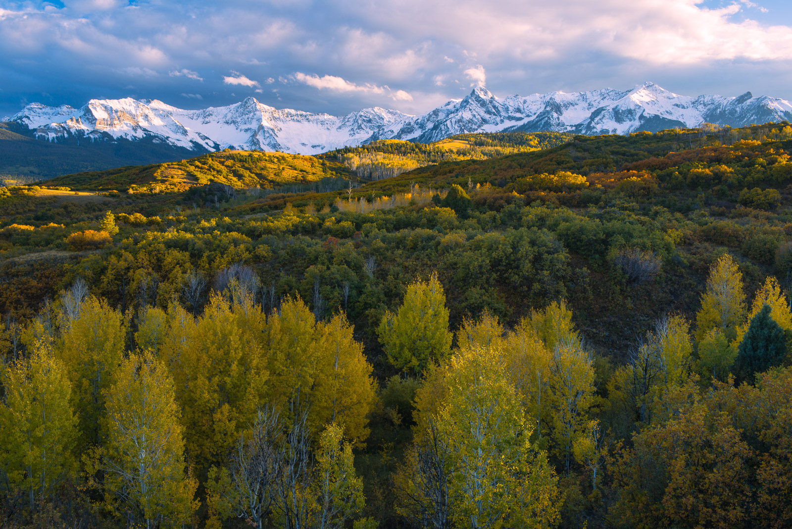 Early snowfall blankets the San Juan Mountains with glorious autumn color captured at sunset.