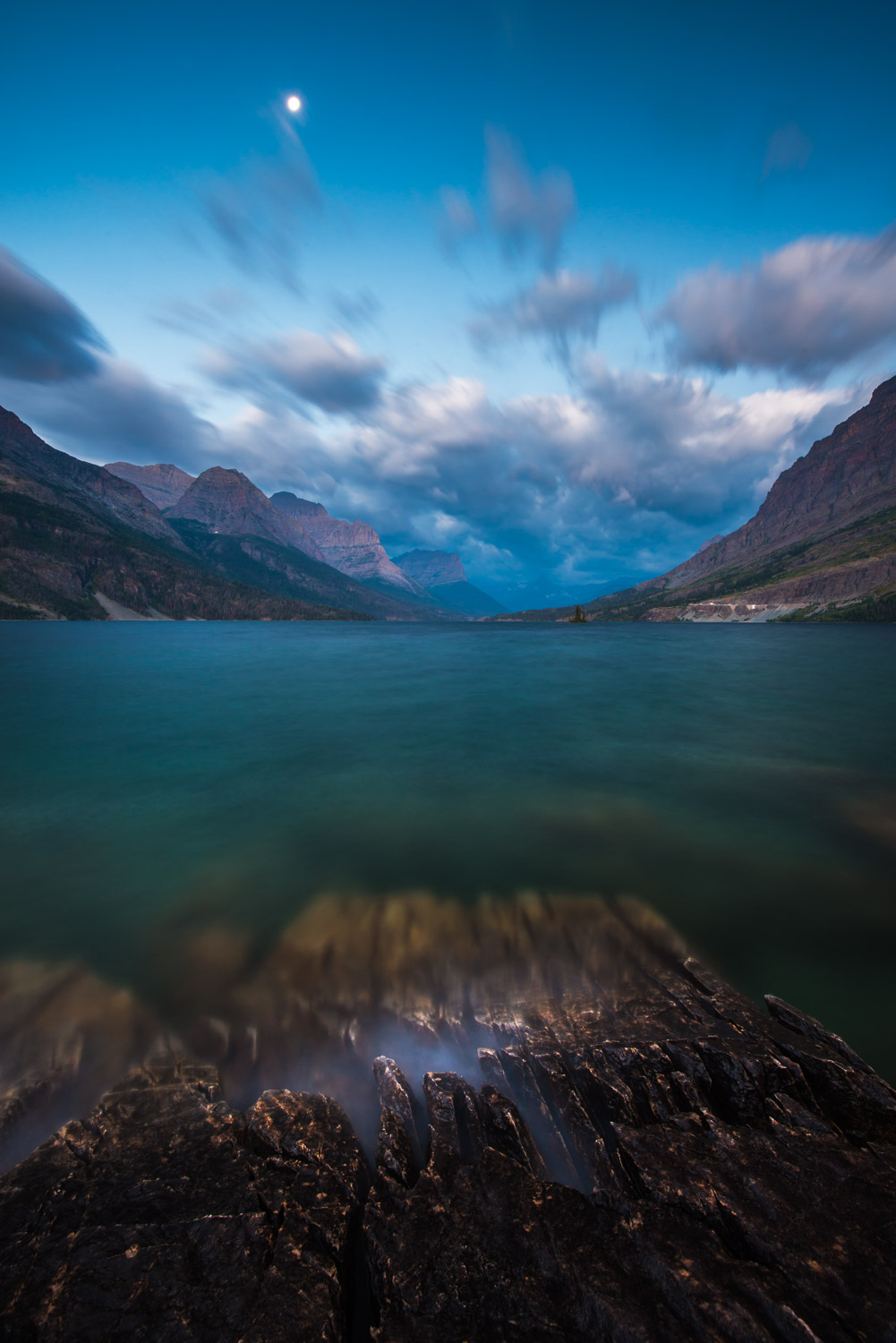 Full moon above St. Mary Lake at twilight in Glacier National Park, Montana.