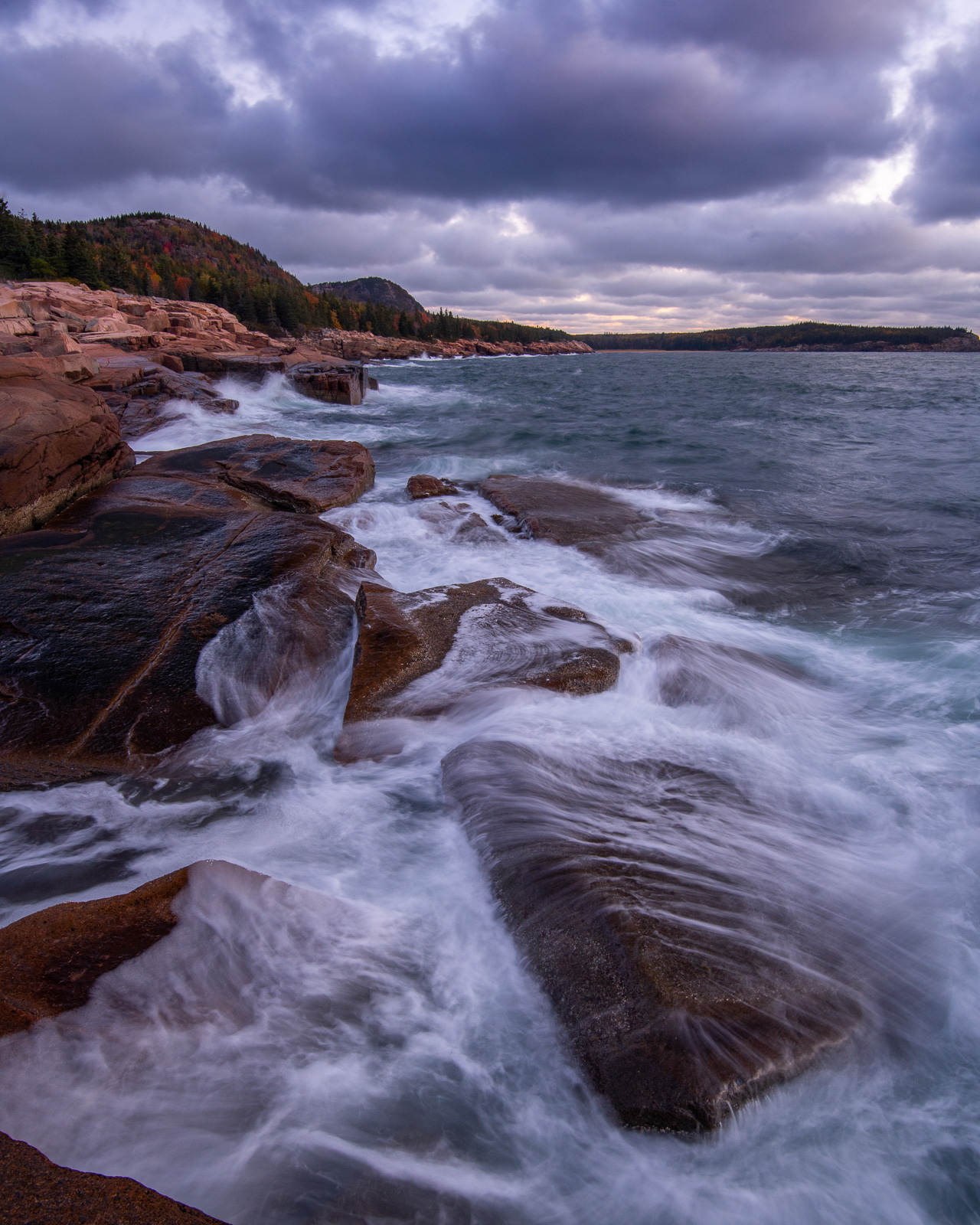 Storm clouds rolling in over the coastline of Acadia National Park at sunrise.