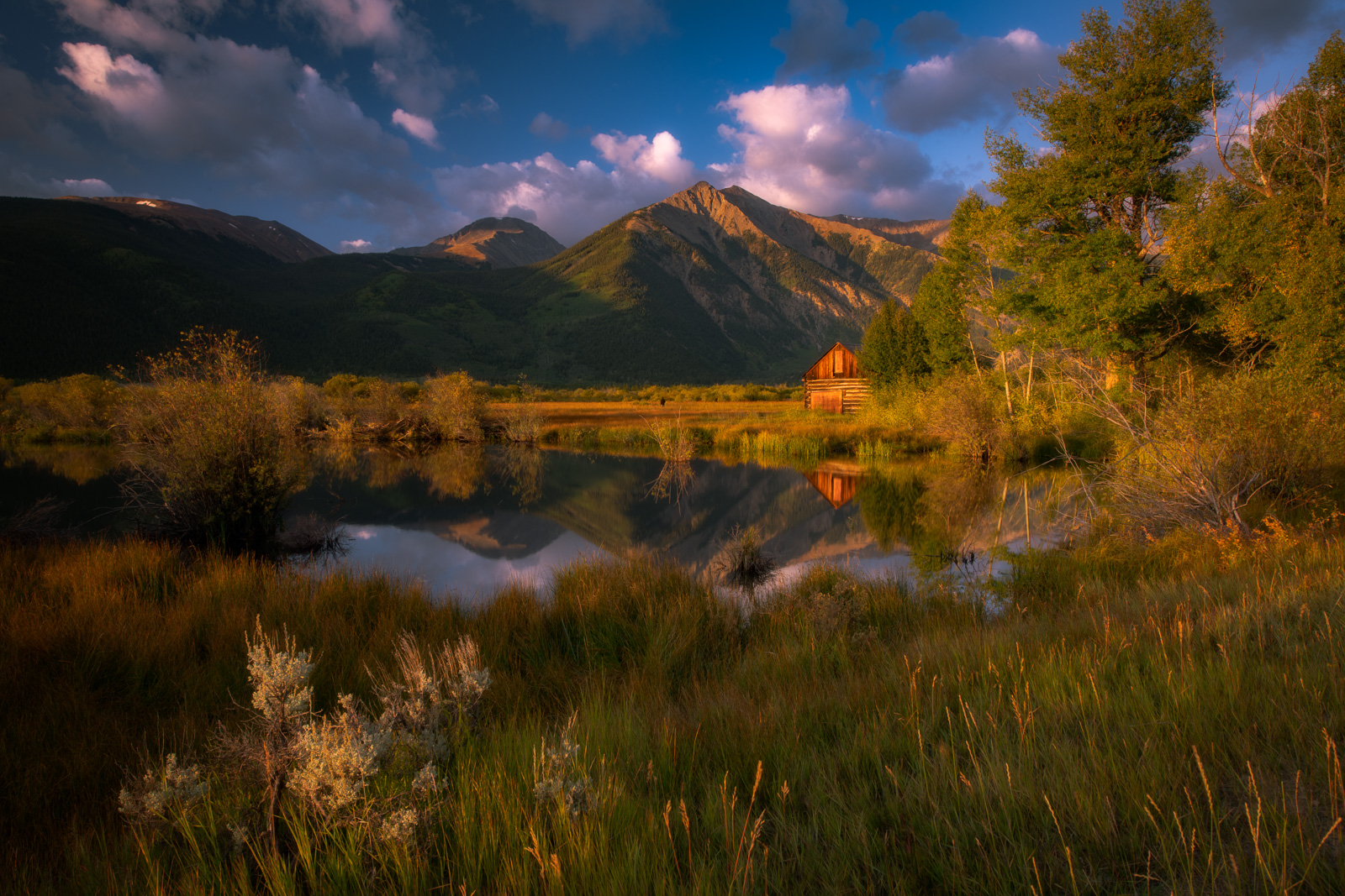 A small cabin and the peaks of the Sawatch Range reflected in Twin Lakes, Colorado.Add beauty to your space with a Joseph Rossbach...
