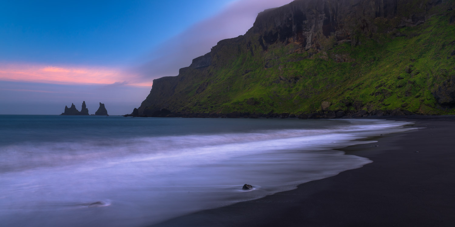 Sea stacks at sunset from the black sand beach outside of Vik, Iceland.