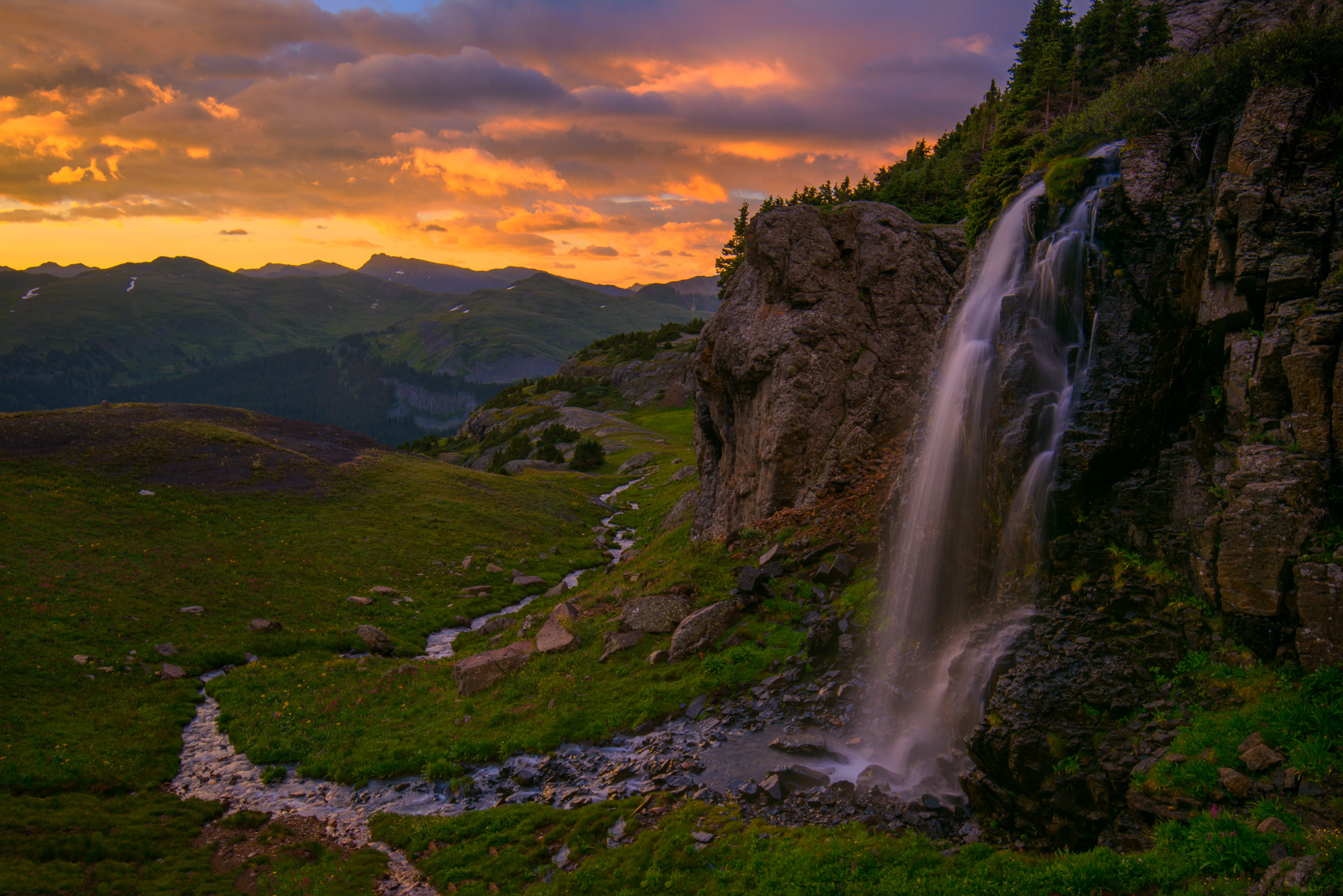 A waterfall in porphyry basin captured at sunset, San Juan Mountains near Silverton, Colorado.