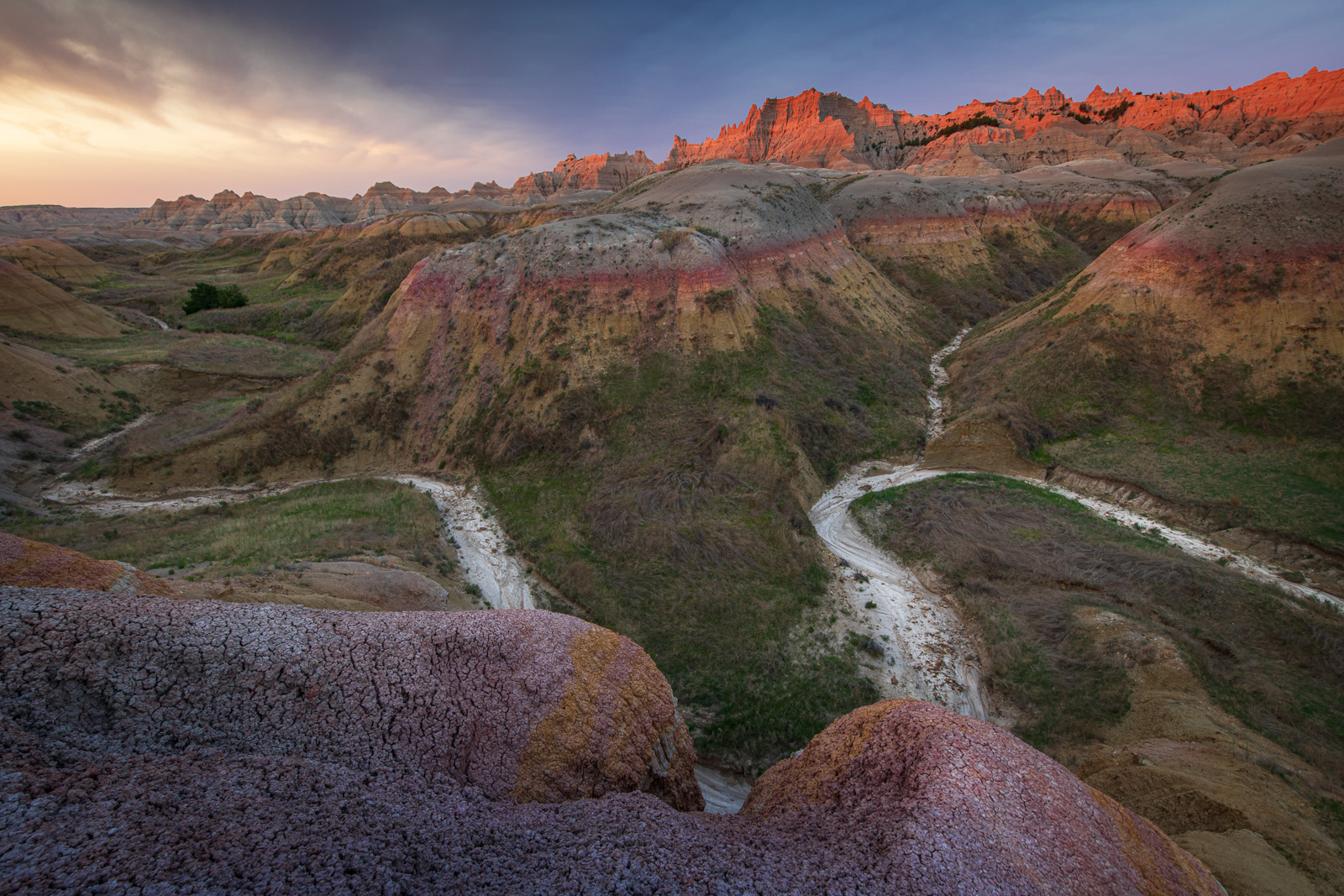 A dry wash snakes below the Yellow Mounds at sunrise.